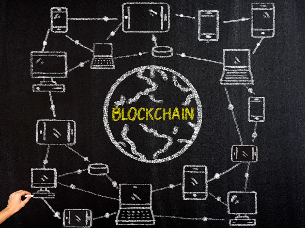 Blackboard with a diagram of a network of computers with the word 'Blockchain' in the middle.