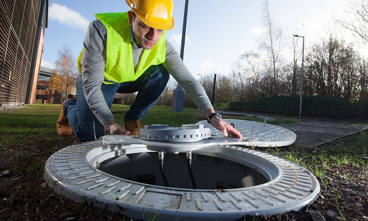 Employee installing a 4G-enabled manhole cover.