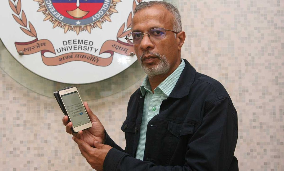CRS Kumar with a mobile phone with the Arogya-Kshema app on it.