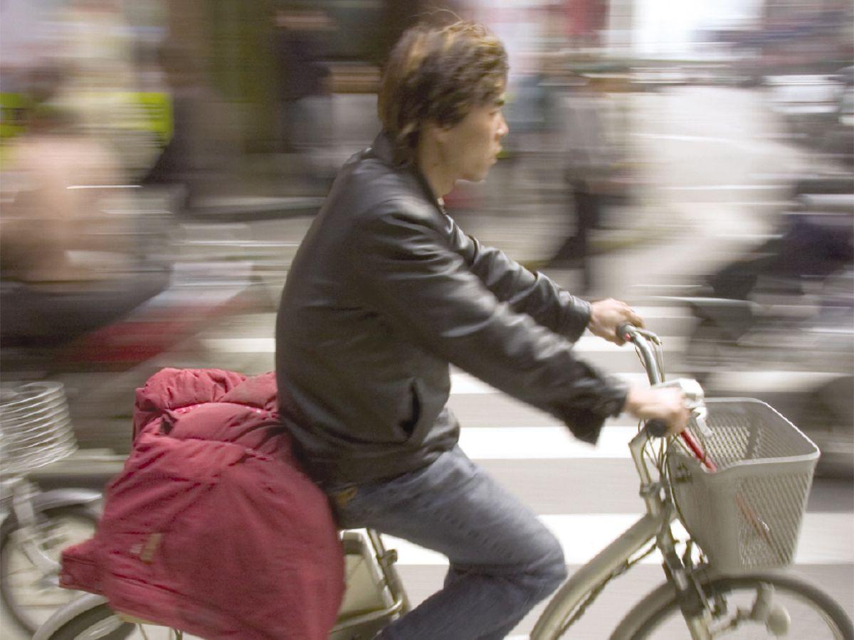 Photo of a man in Shanghai, riding an electric bike along Sichuan Road.