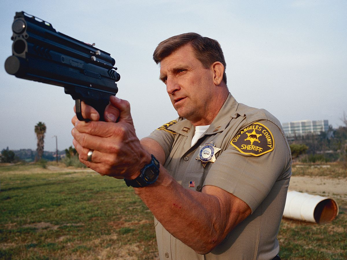Photo of police captain aiming a less-lethal weapon.