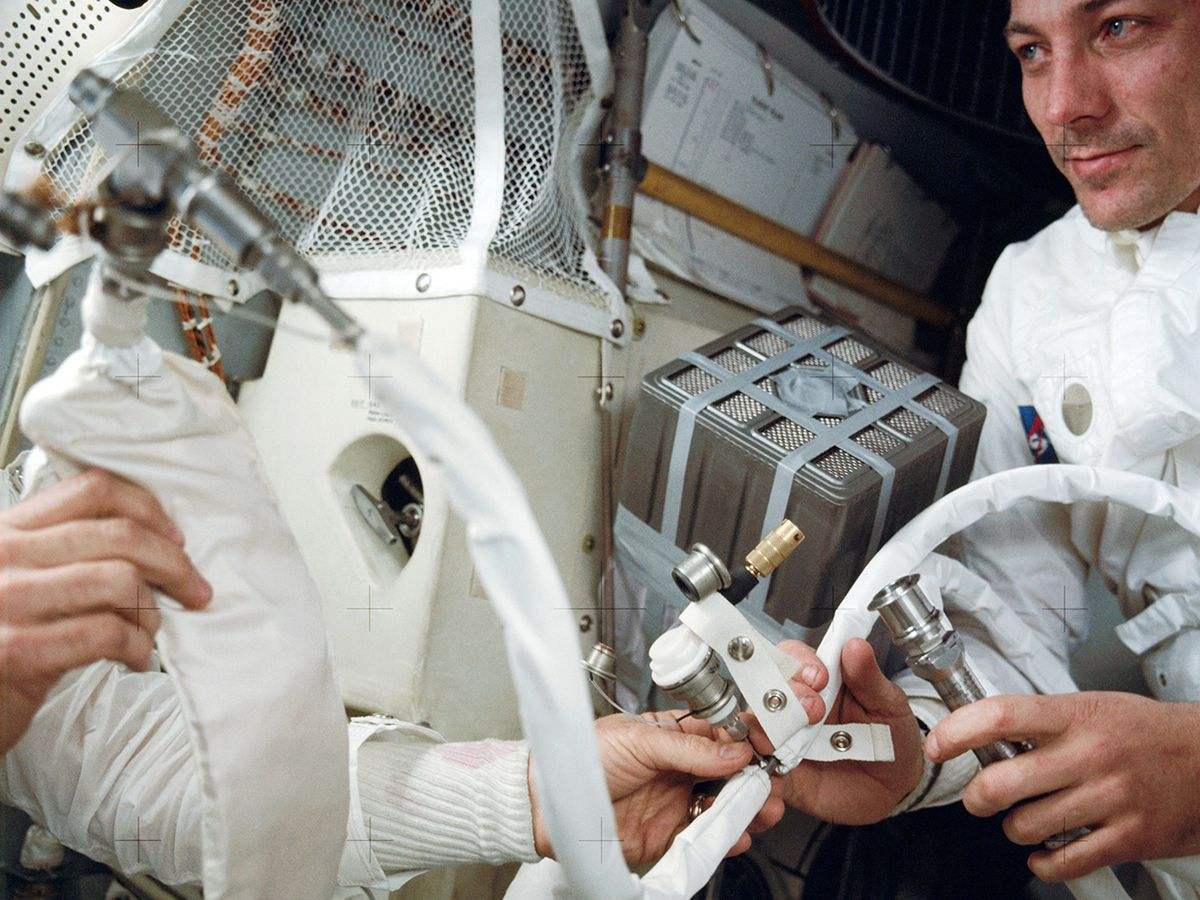 To prevent carbon dioxide poisoning, the crew jury-rigged a filter in the lunar module. Astronaut Jack Swigert is on the left.