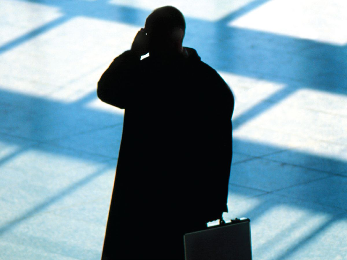 Photo of shadowed man on cell phone.