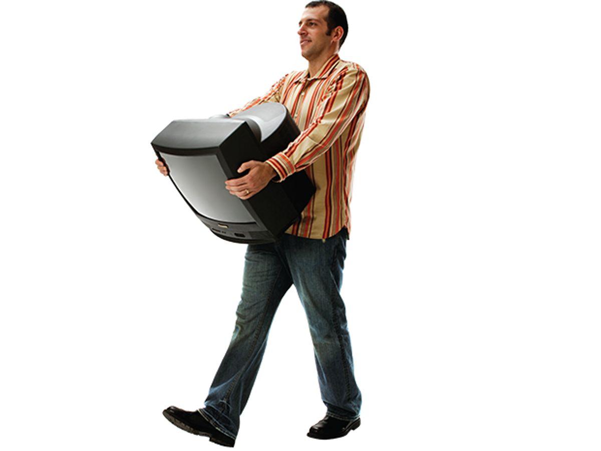 Photo of man carrying TV set.