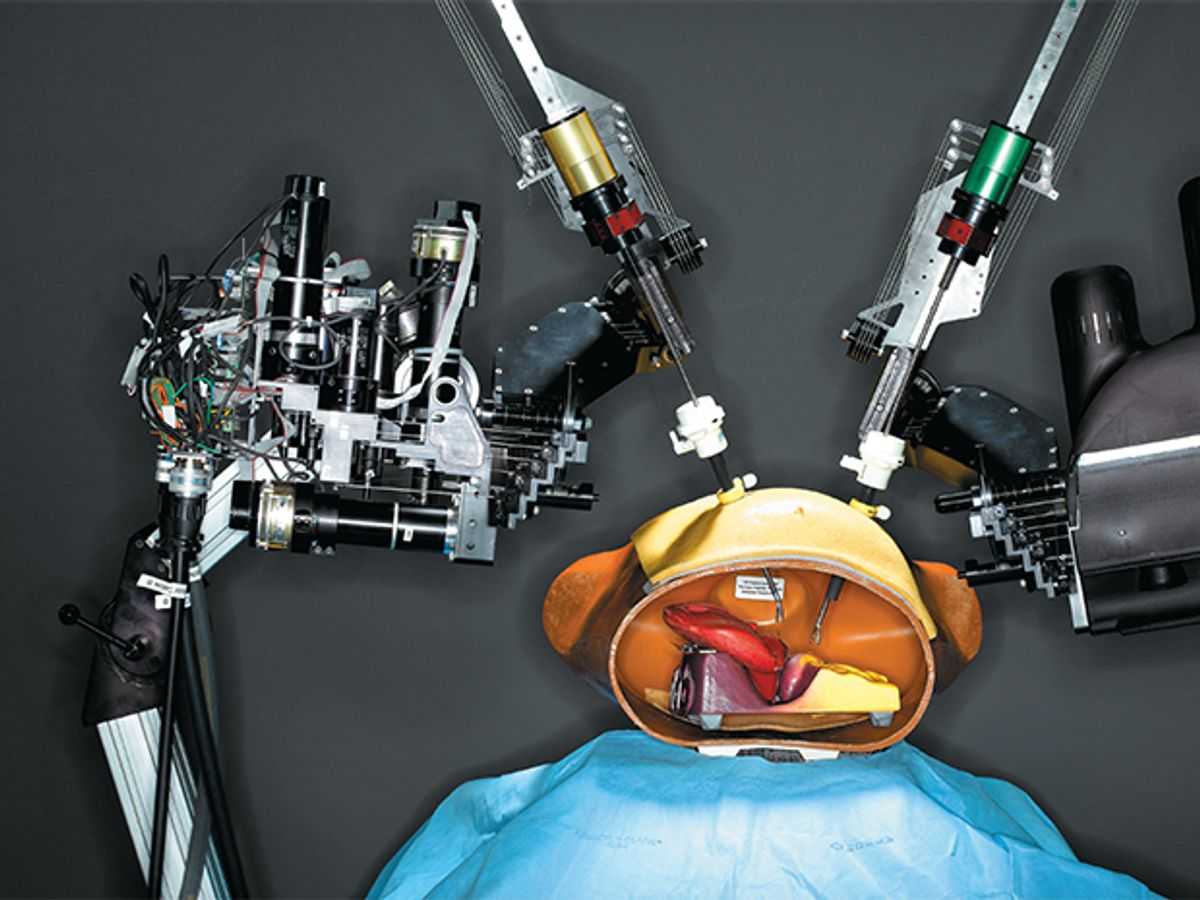 """remote-controlled two-armed surgical robot """"operates"""" on a plastic and rubber anatomical model of a human torso."""