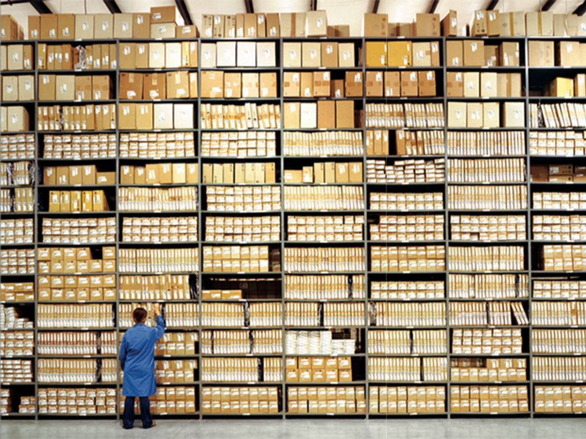 Photo of a man front of a tall shelf of boxes.