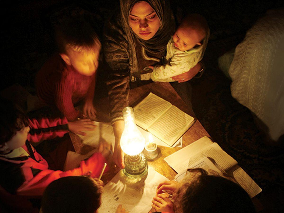 Family huddled over light source.
