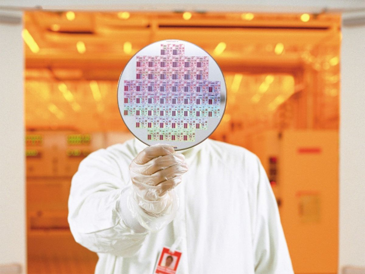 Engineer at Texas Instruments' Kilby fab in Dallas, Texas, holds up a 200-mm wafer containing developmental 64MB ferroelectric RAM chips.