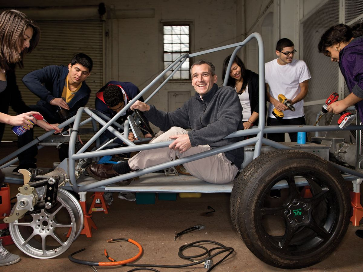 Simon Hauger sits in the frame of a car his students are in the process of building