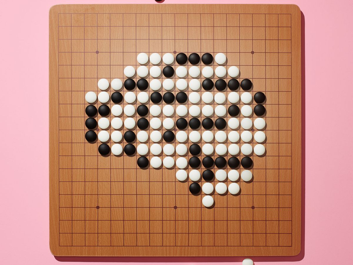 A Go board board covered with a grid of closely spaced lines and bean-size black and white stones.