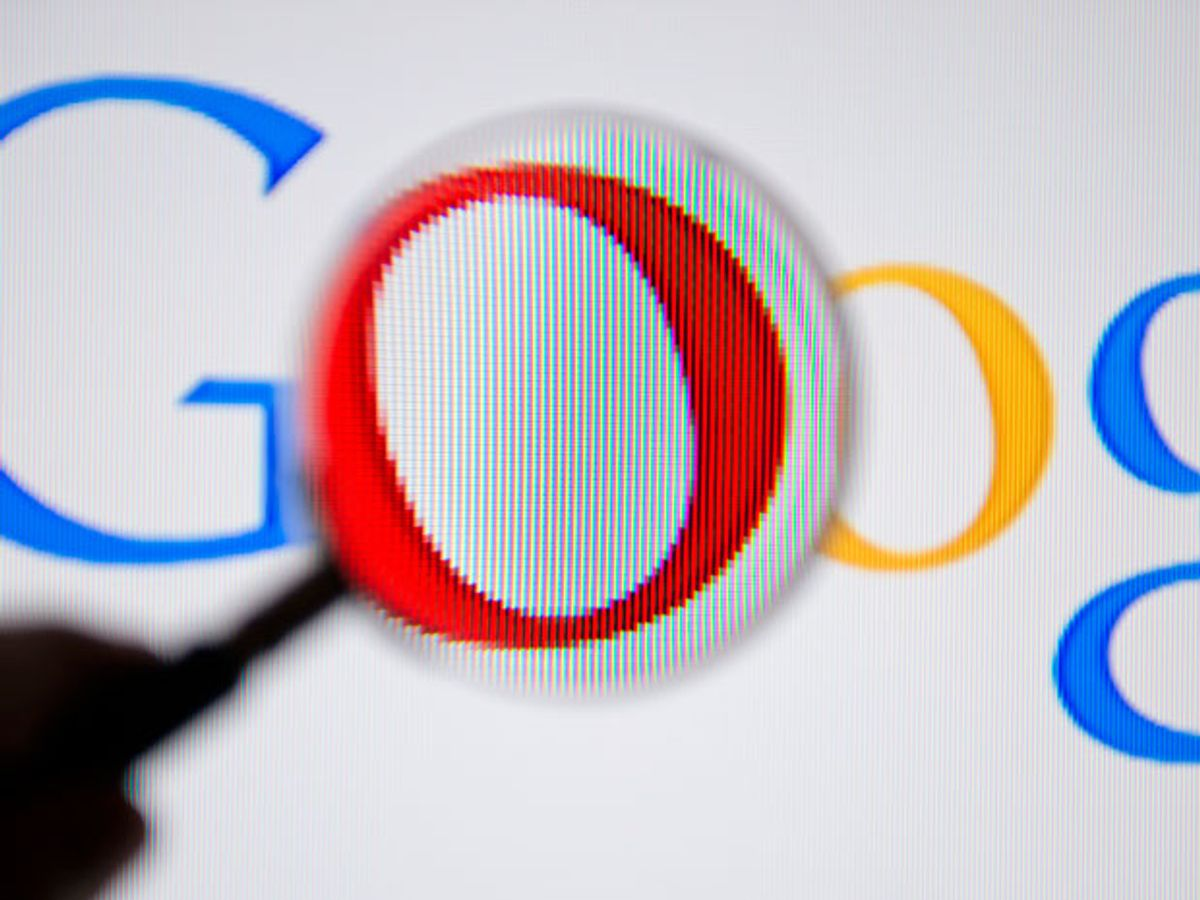 A magnifying glass in front of the Google logo.