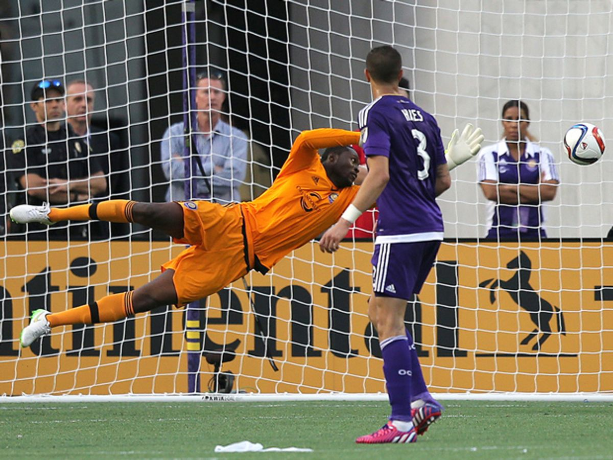 An orange-clad goalkeeper dives towards a soccer ball, while another player in a purple uniform watches