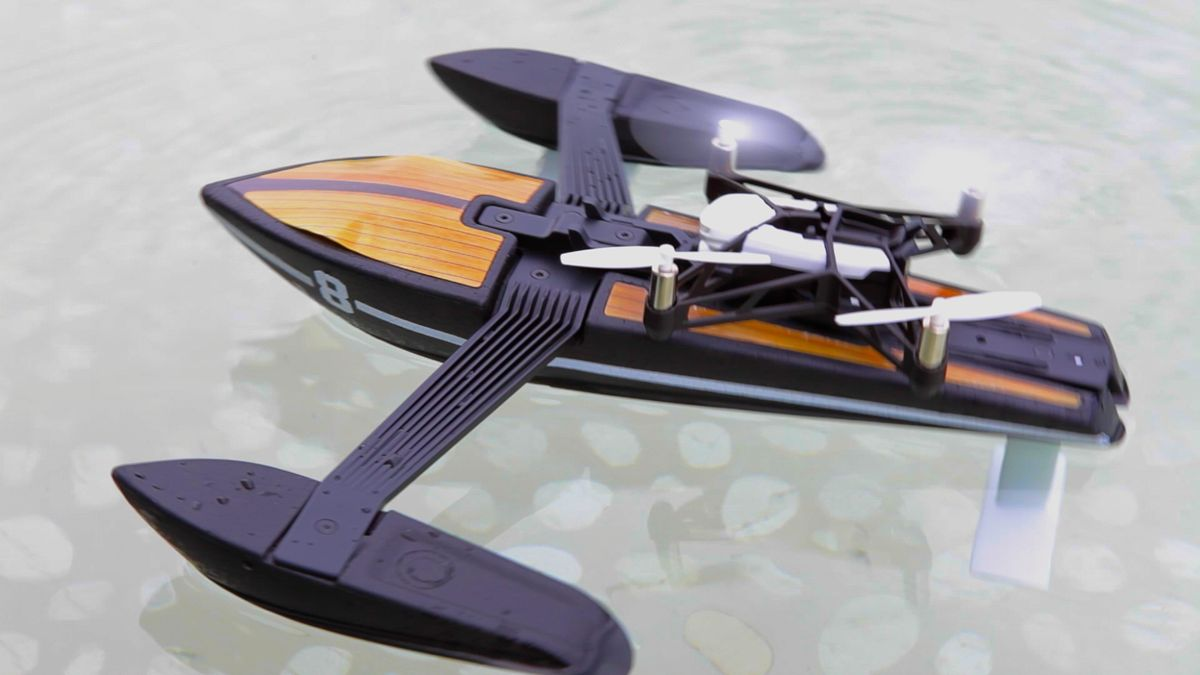 A cameraman-style boat floats in the water, with a quadcopter drone on top.
