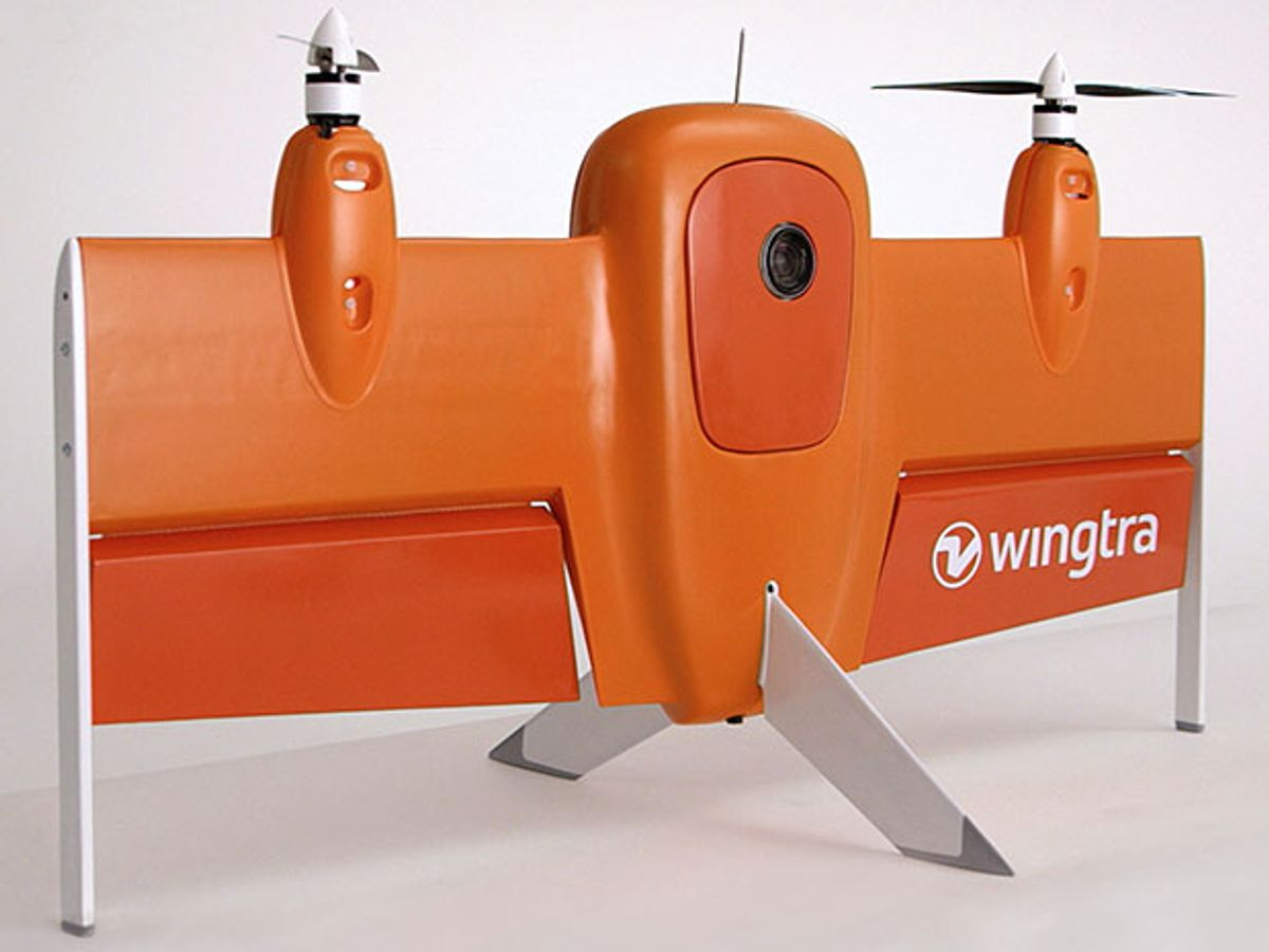 An orange-colored air-plane-shaped drone with two propellers and two large flaps. It is standing vertically, supported by fins from its wings and tail.