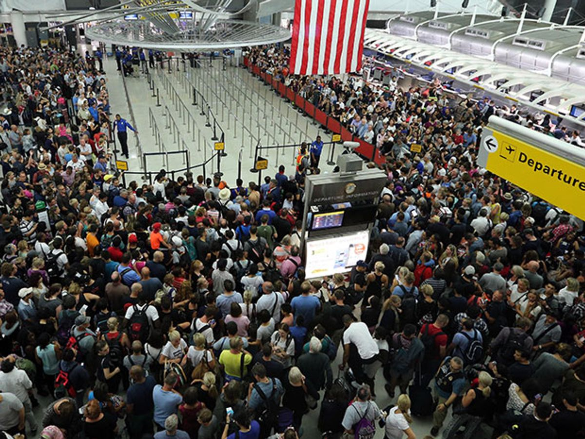 A crowd waits at JFK International Airport due to reports of shooting inside a terminal