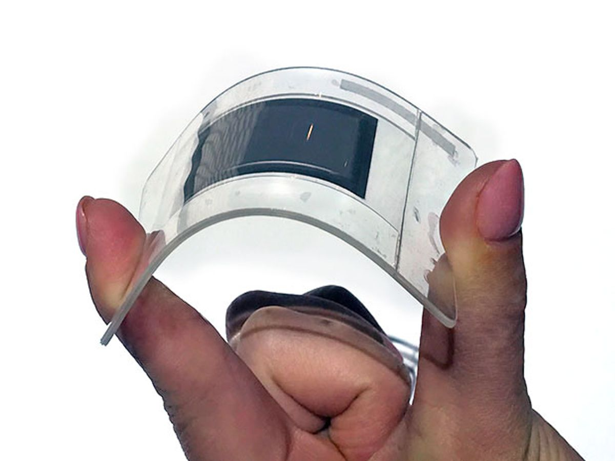 A hand flexing between its fingers a clear plastic sheet with a dark rectangle in the center