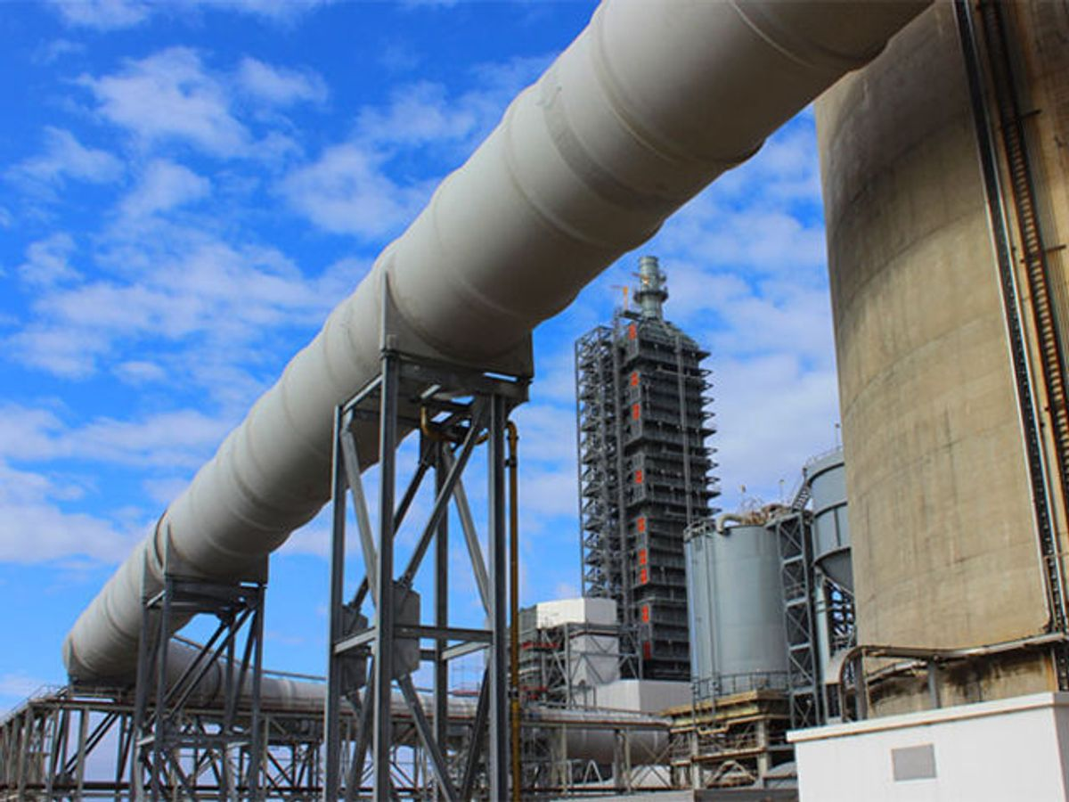 Huge grey pipe on supports winds its way between two parts of the Petra Nova carbon capture facility in Houston