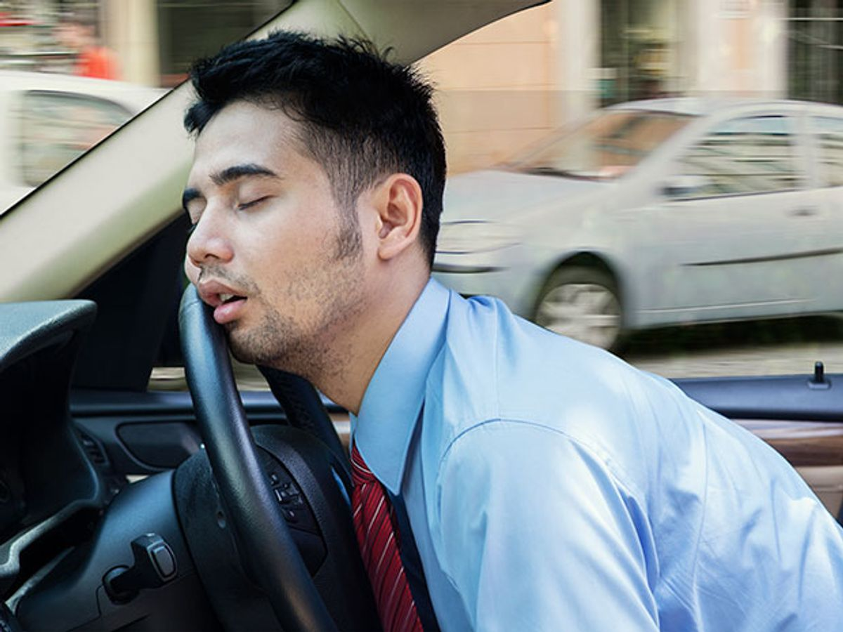 man napping with head against steering wheel