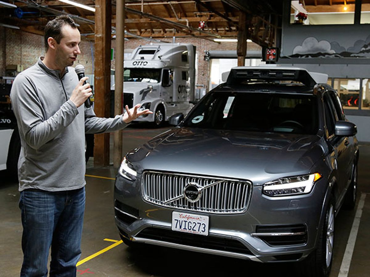 A man, Anthony Levandowski, in a gray shirt holding a microphone speaking in front of a silver sedan.