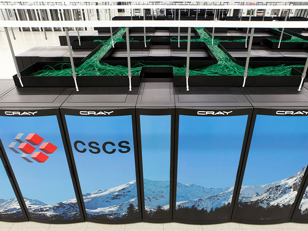 """wall of cabinets show a winter mountain seen. The letters CSCS are visible on one cabinet. The word """"Cray"""" is at the top of each cabinet. Above the cabinets a tangle of green cables extends into the distance."""