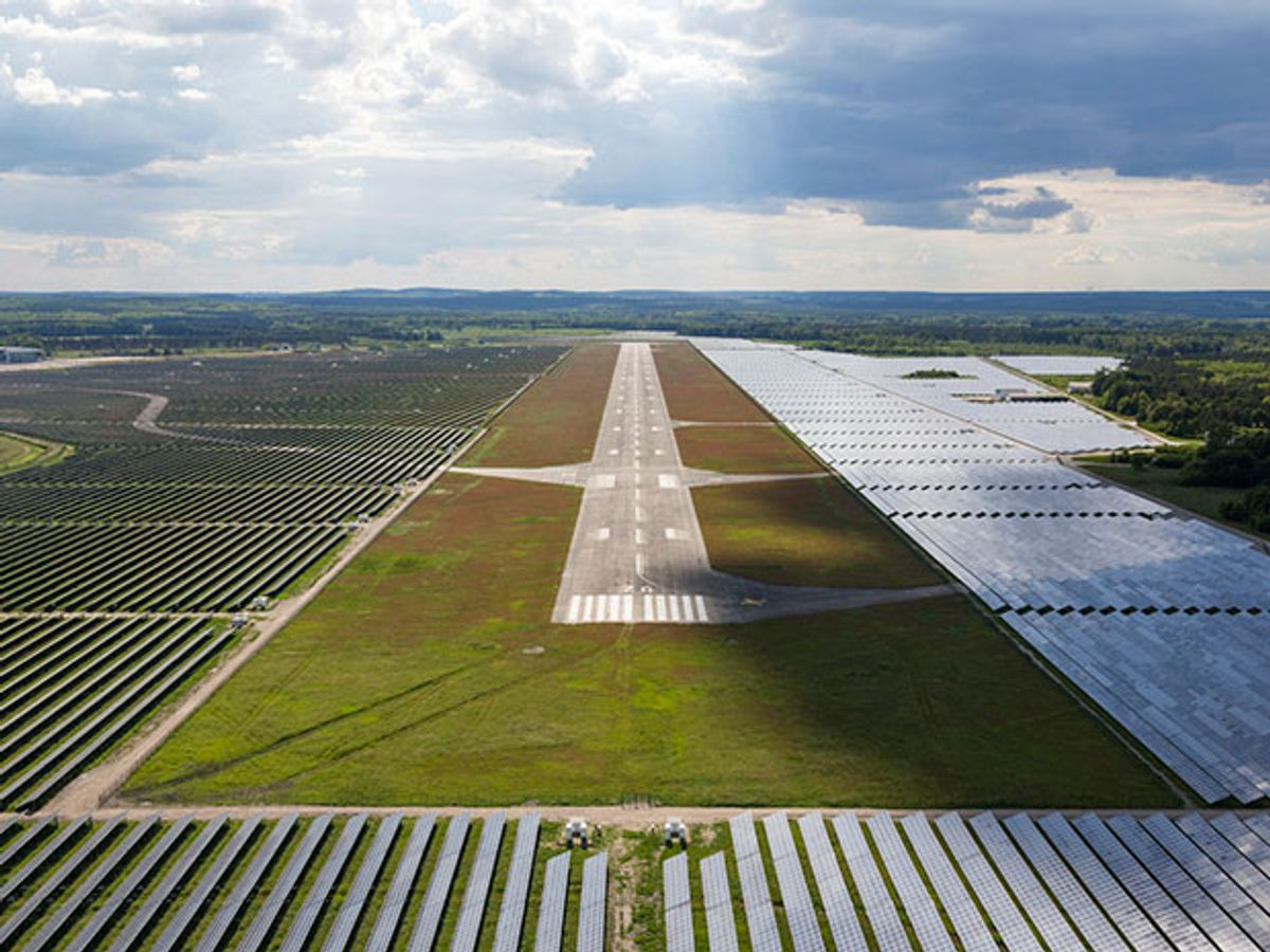 Aerial view of an airport runway with solar PV arrays on all sides of the runway