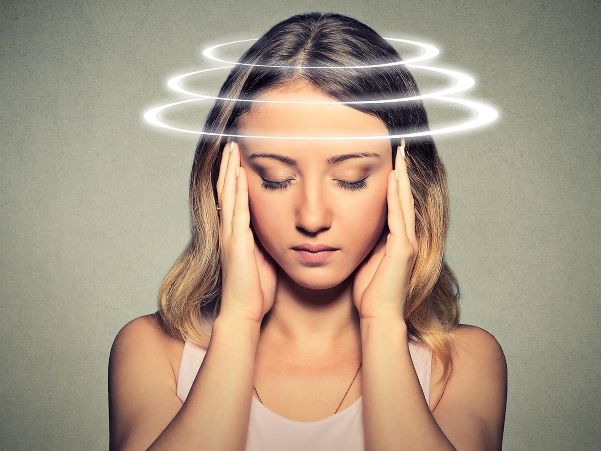 A woman presses her hands to her temples, circular lines around her head indicate dizziness