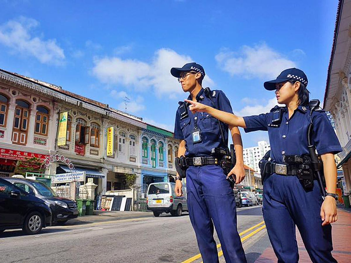 Two police officers dressed in uniform stand to the side of a street in Singapore.