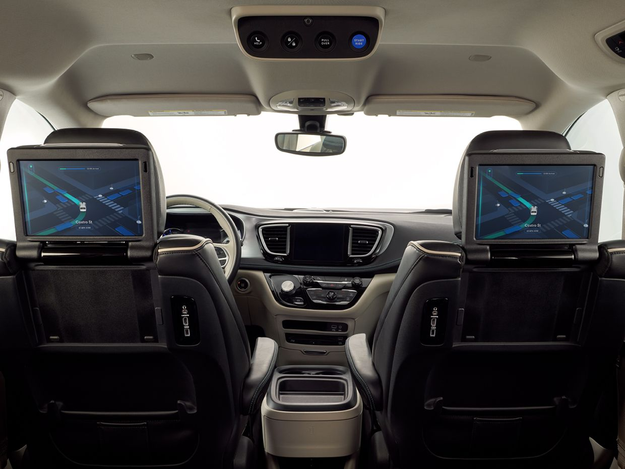Photo inside one of Waymo's Chrysler Pacifica minivans, with no driver, and a display showing the car's progression on the rear of the front passenger seat.