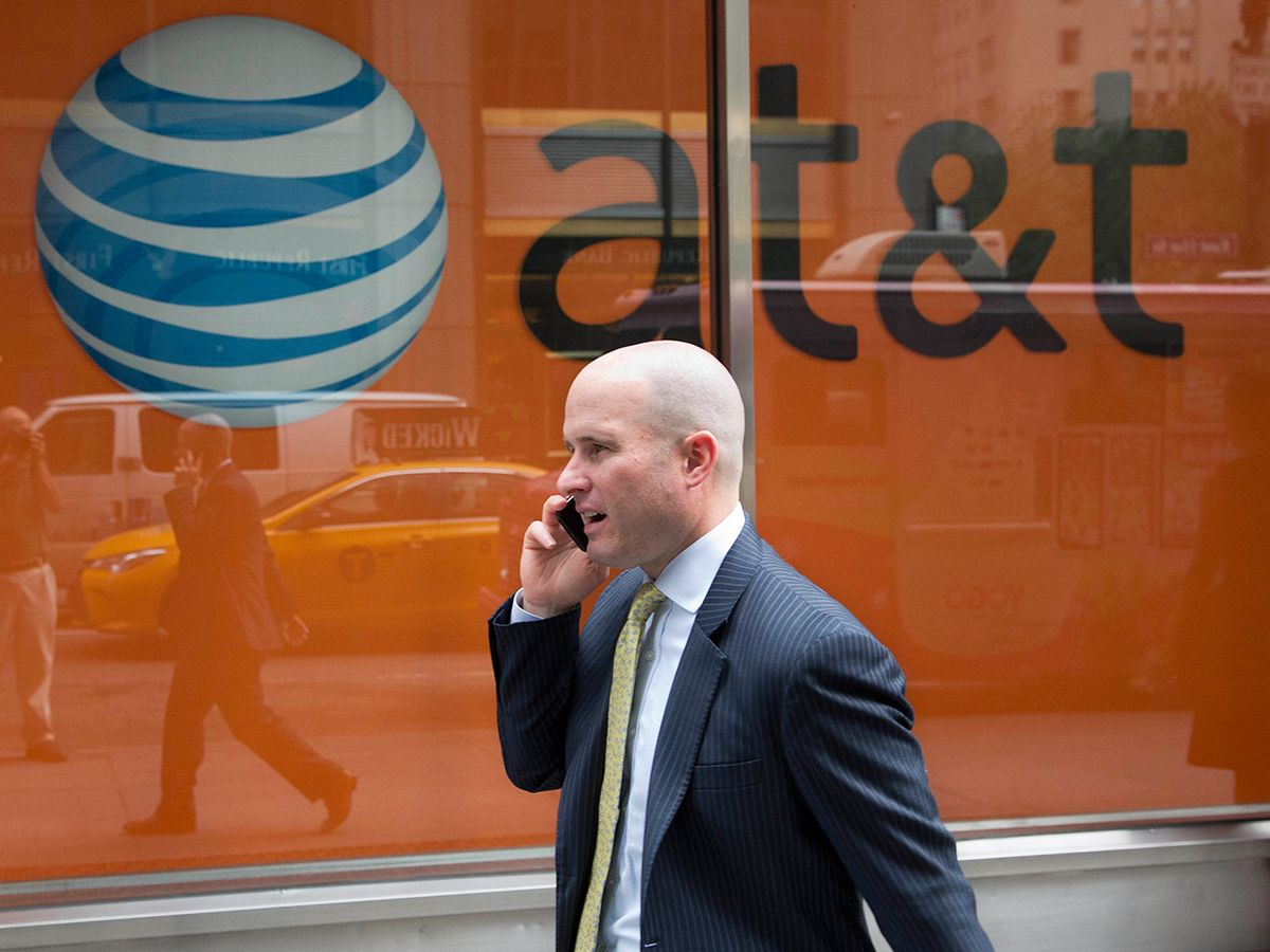 A man using a mobile phone walks past an AT&T store in New York.