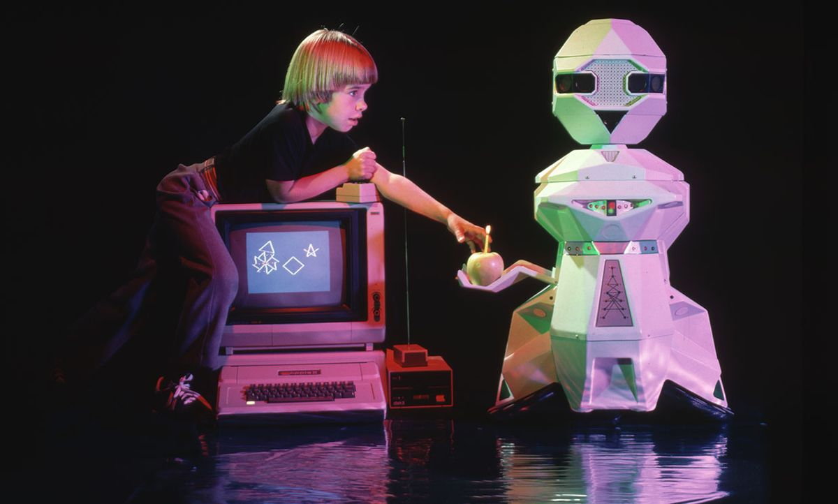 Shawn Melville uses a computer joystick to operate a personal robot. A Topo robot built by Androbot brings him an apple.