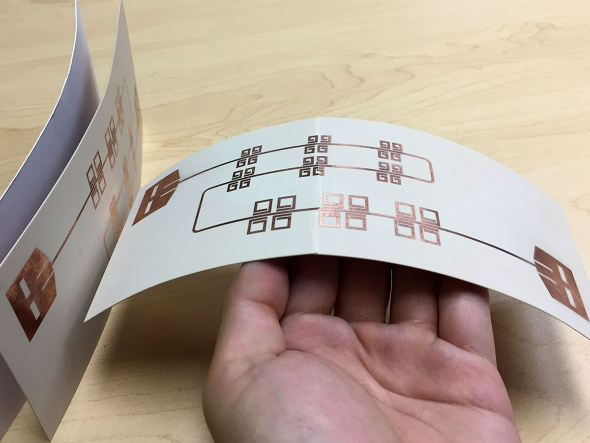 A close-up shows the size of printed thin, flexible LiveTag tags held in someone's hand in comparison with a piece of photo paper on the far left.