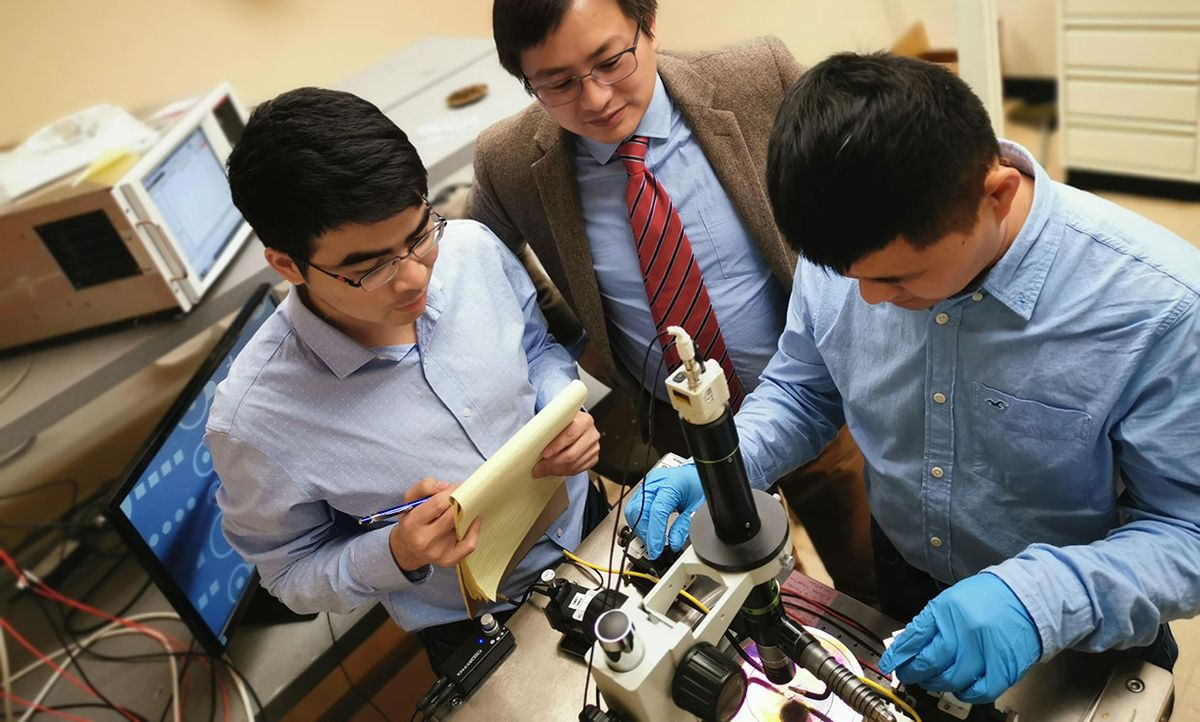 Researchers (from left) Houqiang Fu, Yuji Zhao, Kai Fu work on the memory device at a probe station.