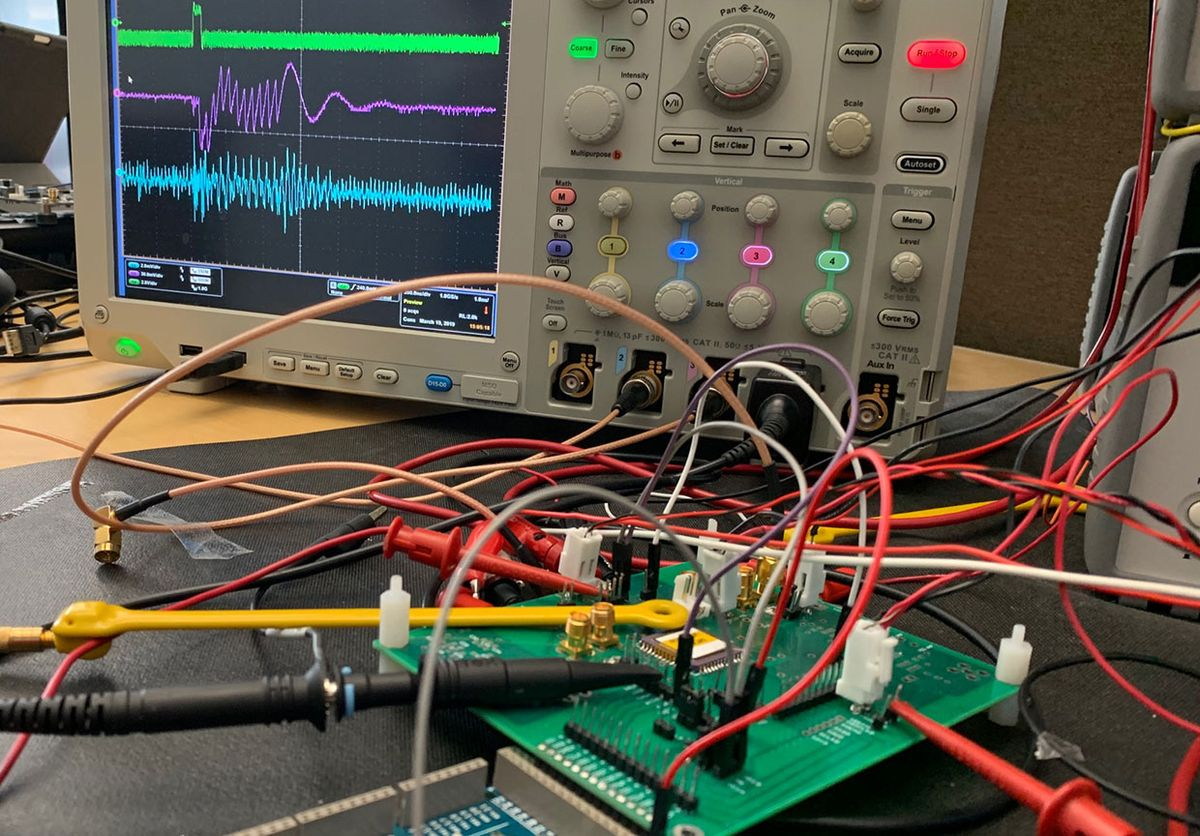 Probe wires are attached to a green circuit board. An oscilloscope displays multiple traces in the background.