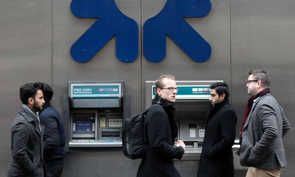 Pedestrians walk past automated teller machines (ATMs) at a Royal Bank of Scotland Group Plc branch in London, U.K., on Thursday, Jan. 26, 2017.