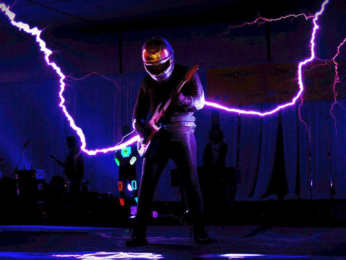 Photo showing that ArcAttack makes its own Tesla coils to produce giant sparks for live performances—and a wearable Faraday cage to perform in.