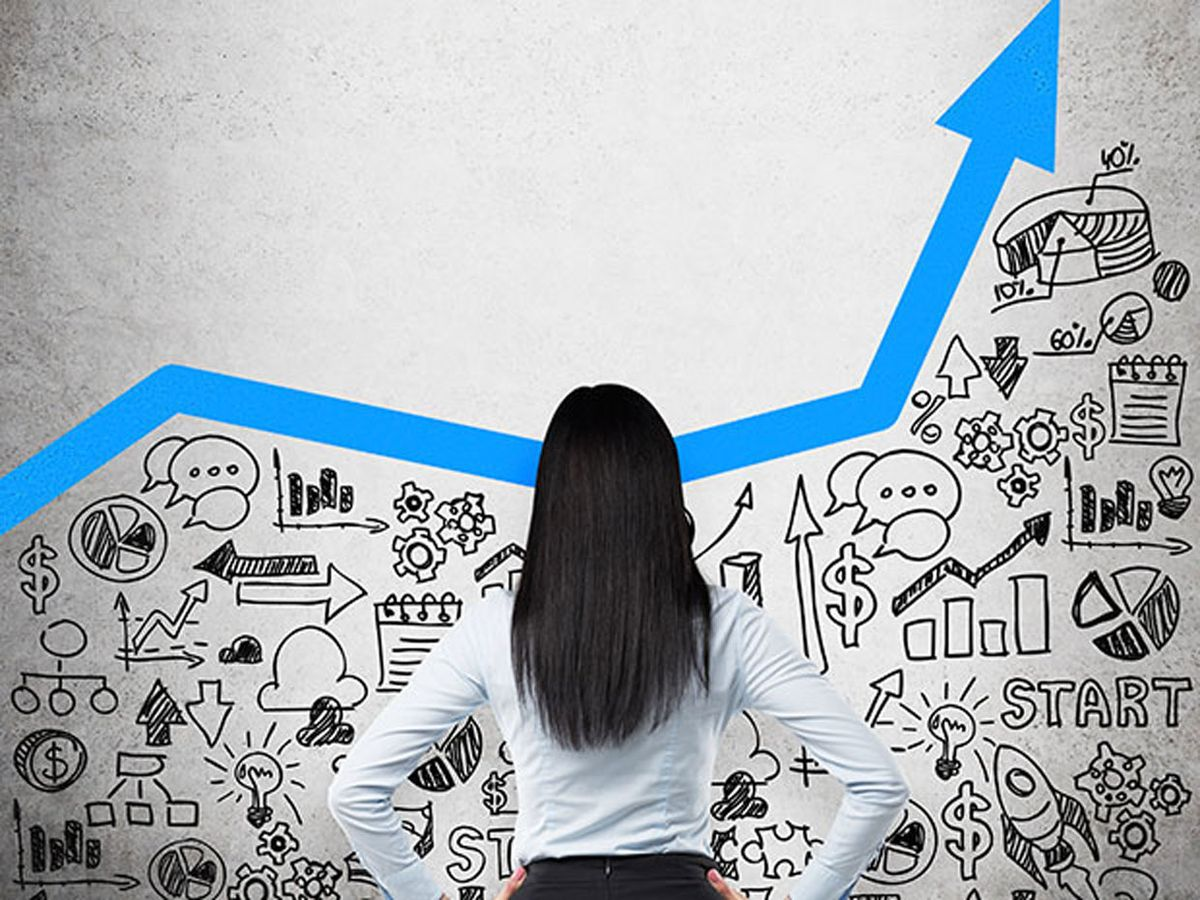 Photo of a woman standing in front of a bar chart with illustrations below it.
