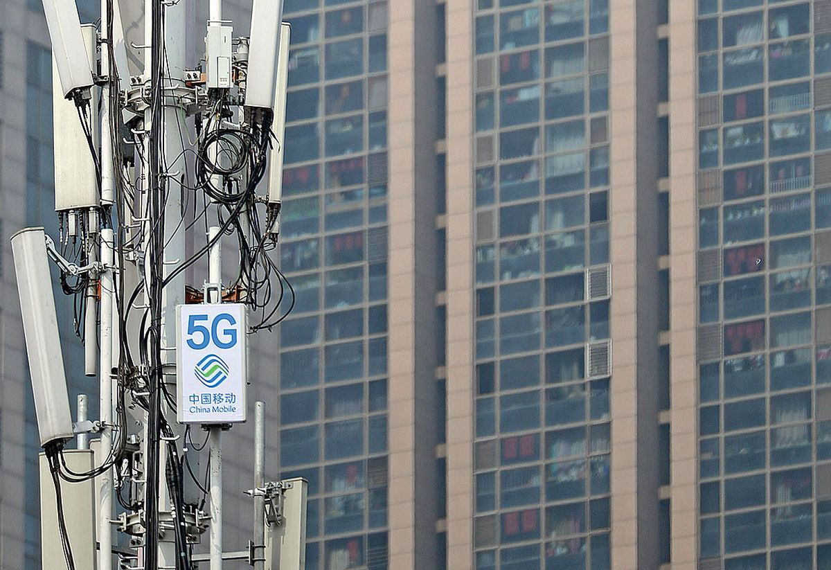 """A group of cellular antenna with a sign for """"China Mobile"""" and """"5G."""""""