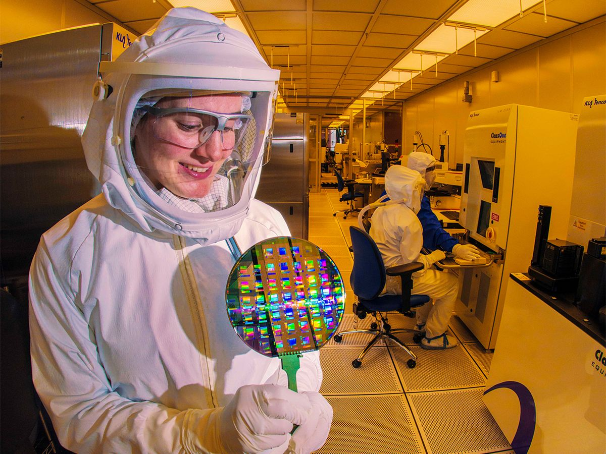 A microelectronics technician at Sandia National Laboratories studies a wafer, a thin slice of semiconductor material used in integrated circuits.