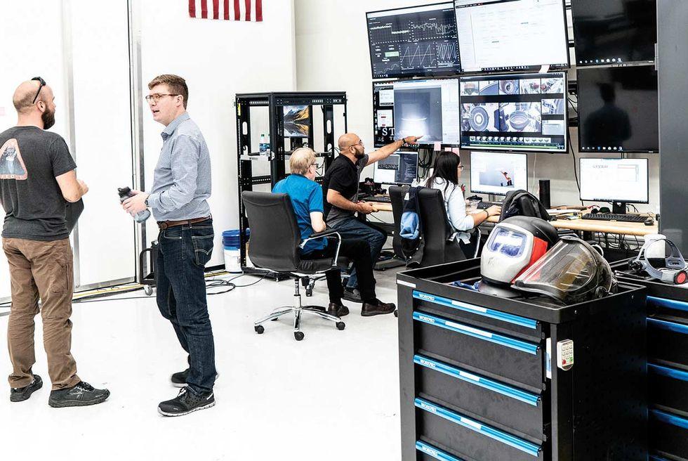 Engineers talking and looking at monitors.