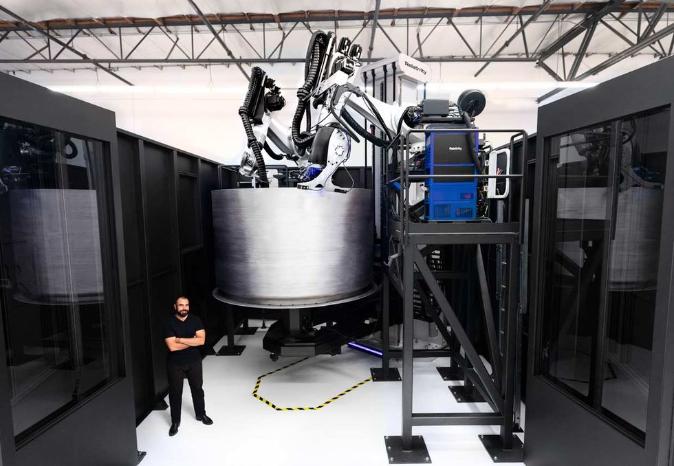Jordan Noone, Relativity Space cofounder, stands in front of the companyu2019s newest 3D printer as it builds a fuel tank for the Terran 1 rocket.