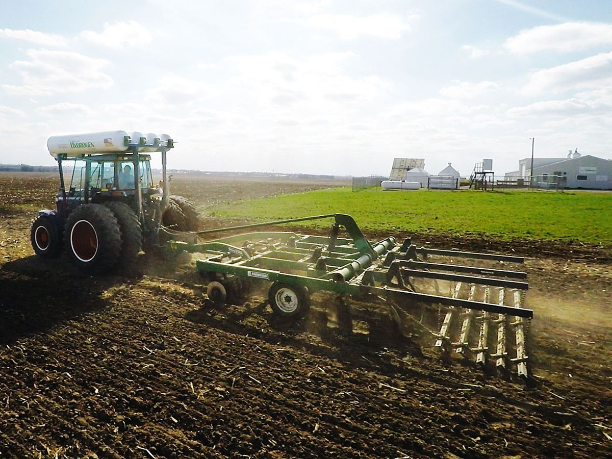 A tractor pulling a farm implement in a field.