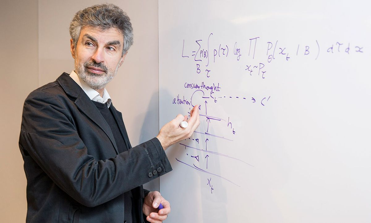 Yoshua Bengio in front of a white board with equations.