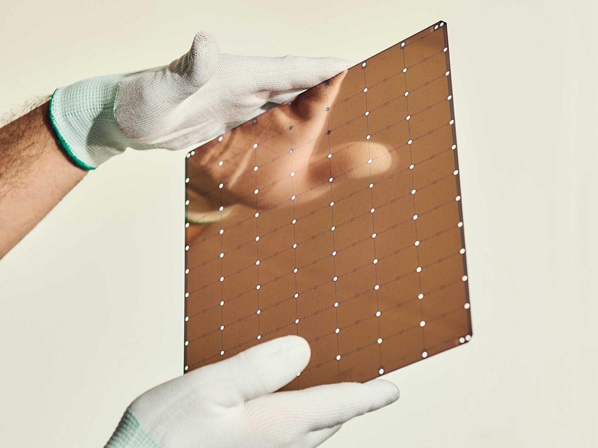 Photo of gloved hands holding wafer-scale chip.