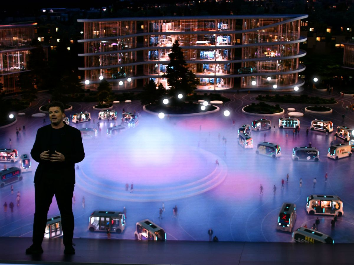 A man stands in front of a colorful rendering of passengers and self-driving cars in Toyota's Woven City.