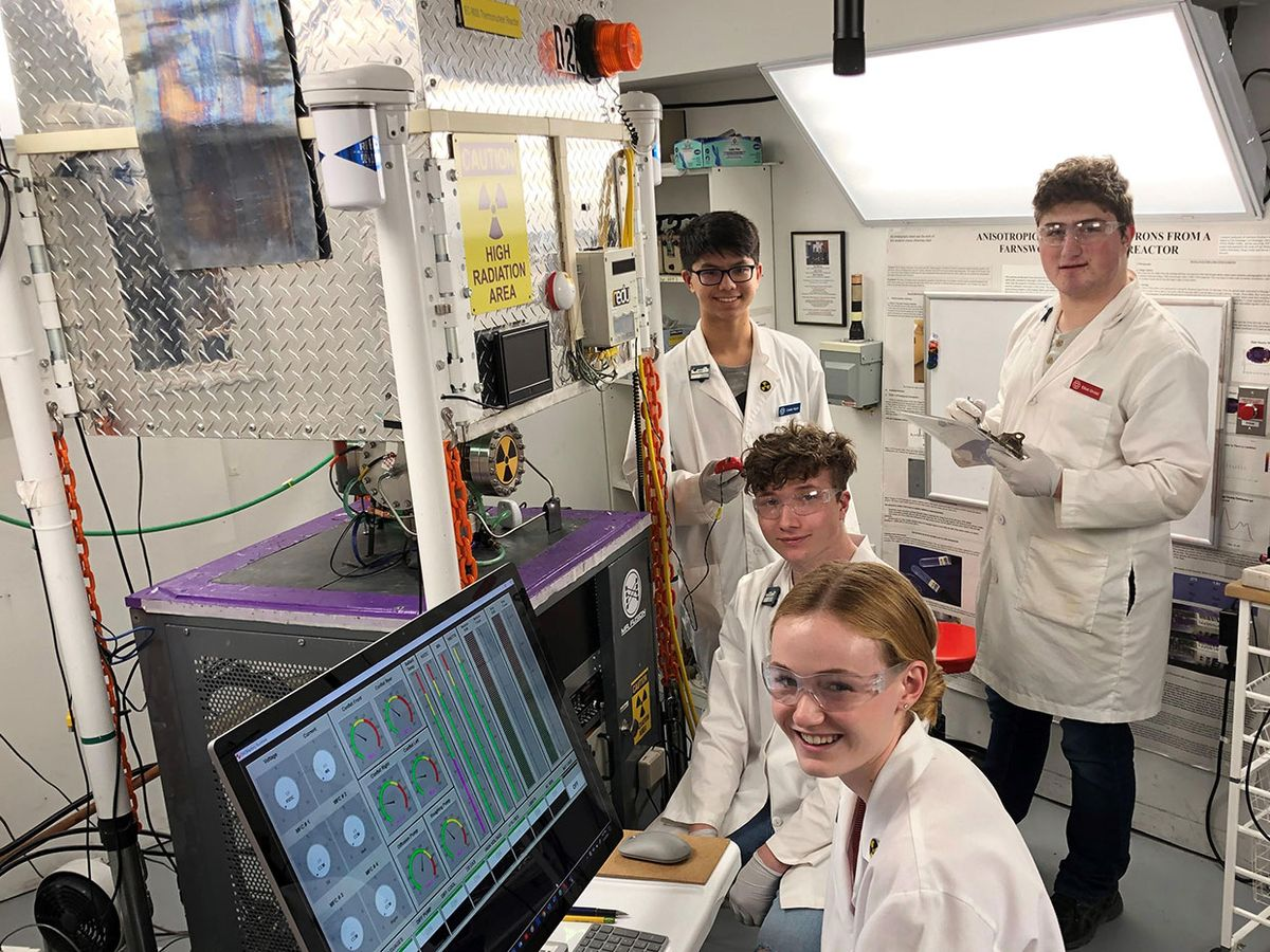 Students pose in Carl Genoinger's basement while working with his 60-kilovolt Farnsworth-Hirsch fusion reactor.