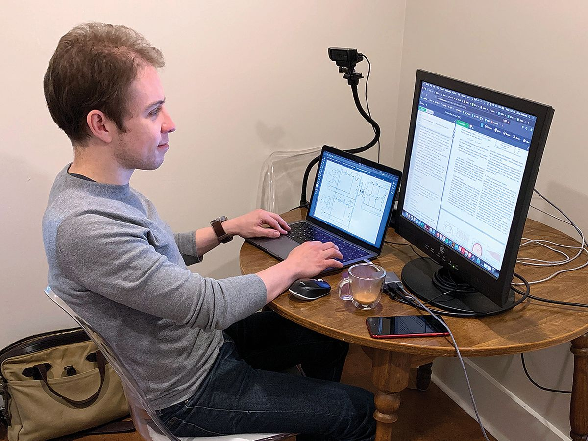 A man sitting in front of a laptop computer and monitor.