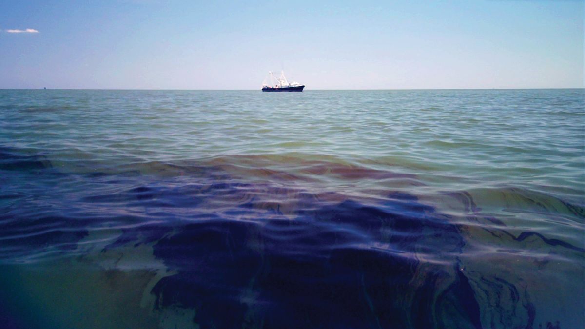 Oil in the water with a tanker on the horizon.