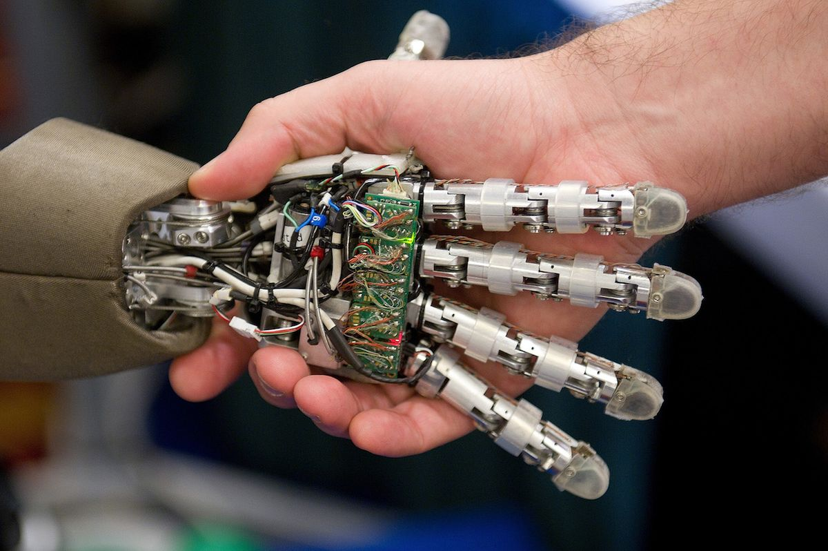 iCub humanoid robot shakes hand with a person