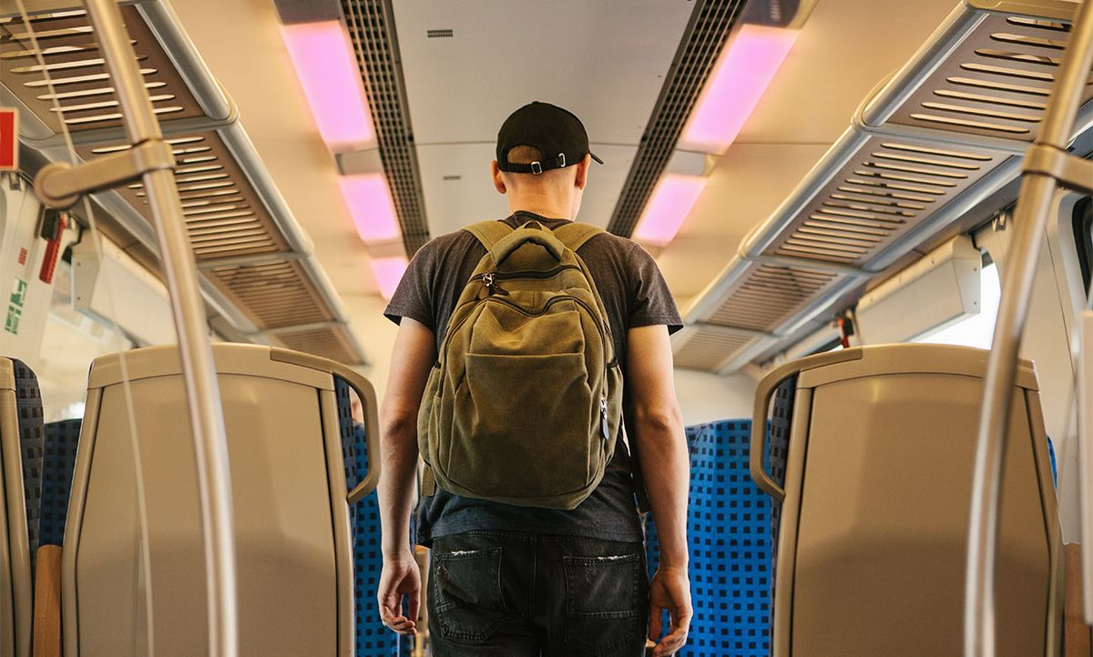 Conceptual photo illustration of a man on a train. The lights are shaded a color to indicate that they could contain far-UV light fixtures.