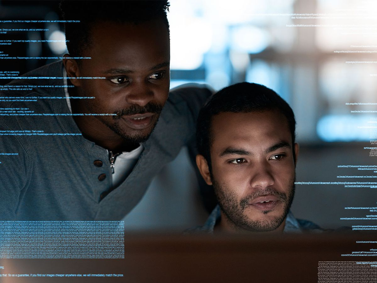 Two black software programmers look at a screen together.